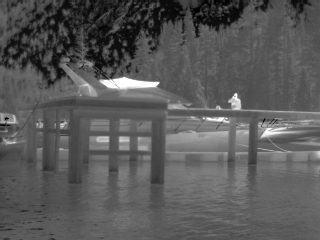 FLIR white hot image of a man on boat dock