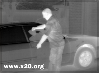 A man breaking into a car as seen with the mid wave thermal imager